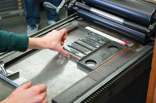 Putting lines of type onto the bed of the press